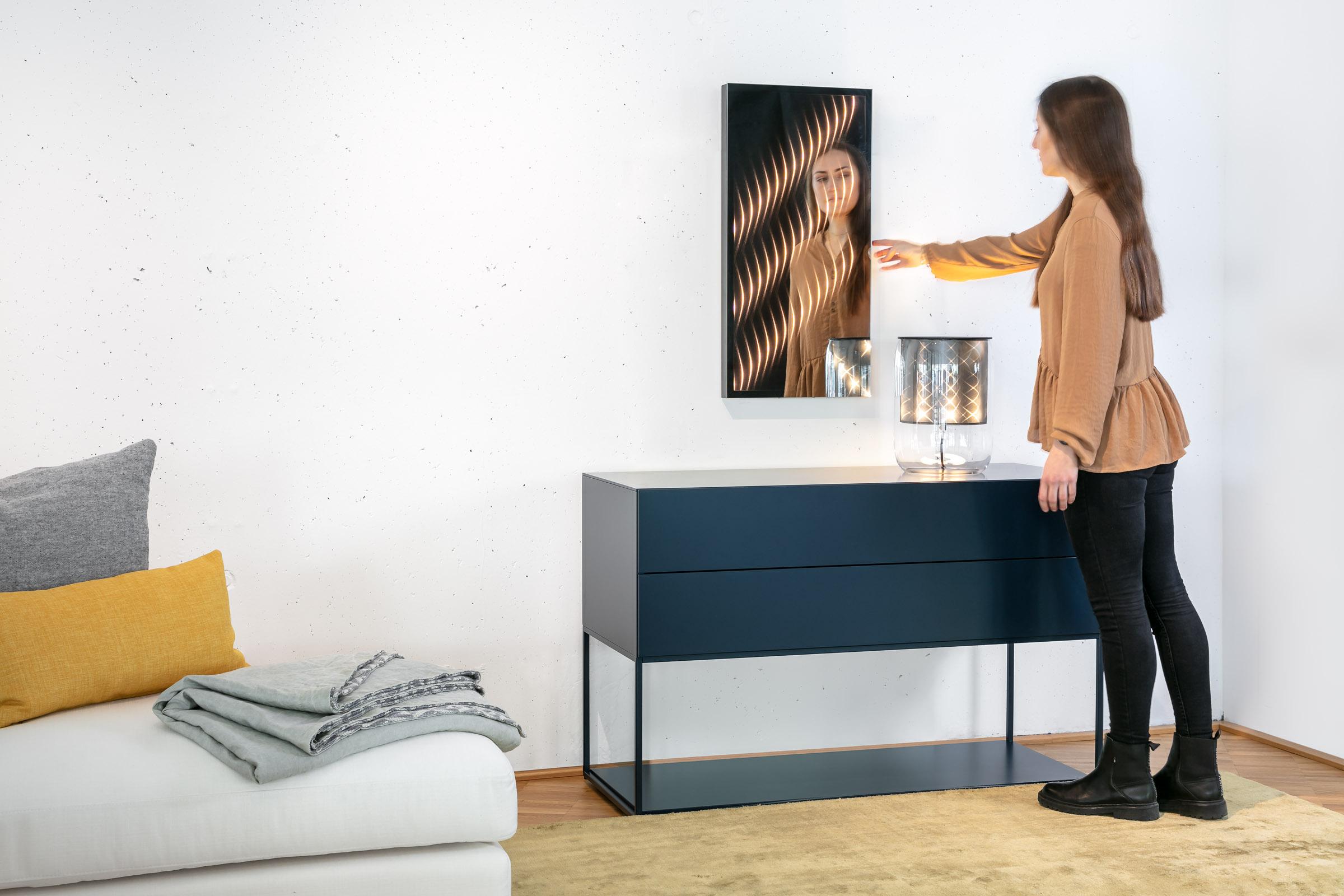 Junge Frau schaltet den kleinen Ambiloom® Wandspiegel am Touchpanel ein