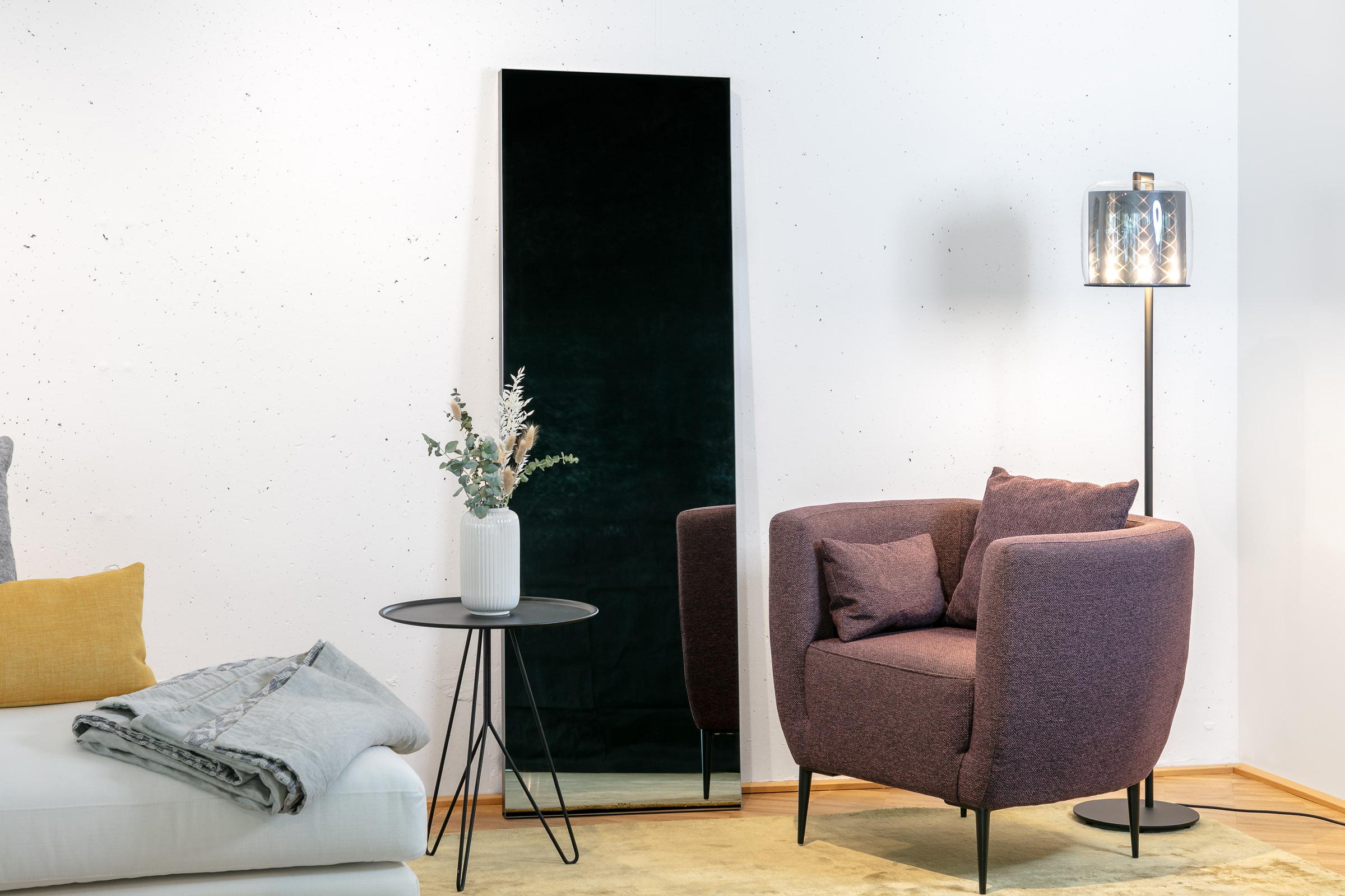 Der Ambiloom® Ganzkörperspiegel ohne Licht an weißer Wand angelehnt vor einem Sessel