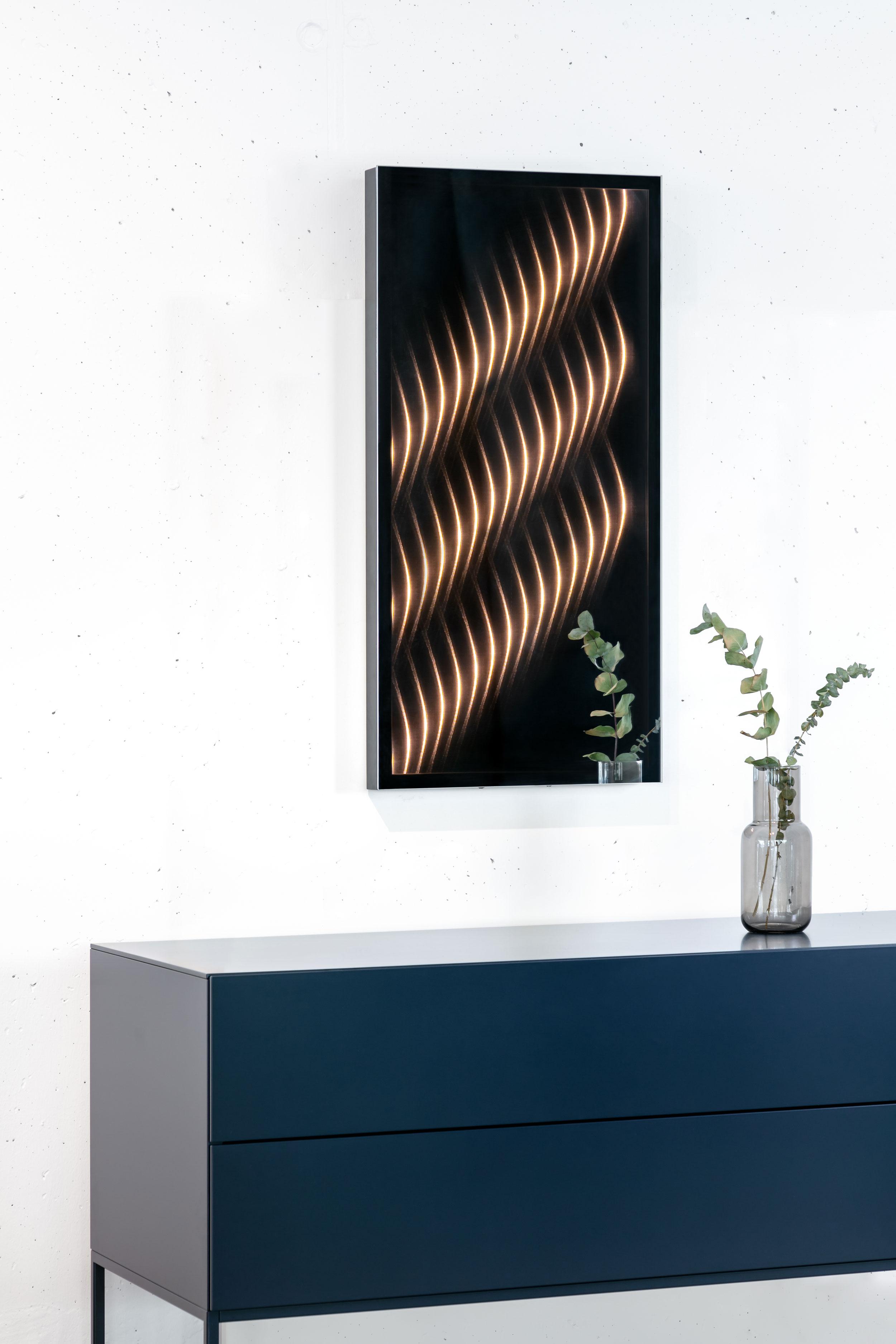 Der Ambiloom® Spiegel mit eingeschaltetem Licht an einer weißen Wand hängend