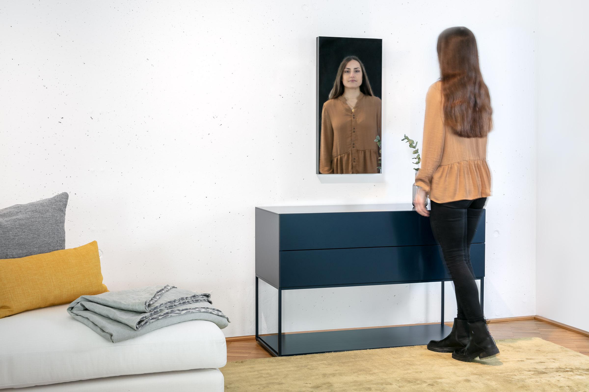 Junge Frau sieht sich im Ambiloom® Wandspiegel an, der über einer Kommode hängt